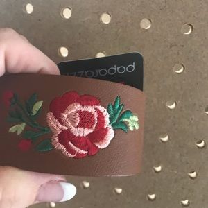 Faux leather wrap with/red flower embroidery.